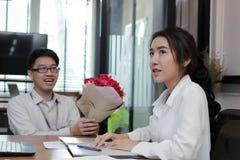 Jeune femme asiatique gaie acceptant un bouquet des roses rouges de l'ami dans le bureau le jour du ` s de valentine Histoires d' Photographie stock