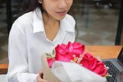 Jeune femme asiatique gaie acceptant un bouquet des roses rouges de l'ami le jour du ` s de valentine Histoires d'amour dans le l Photographie stock libre de droits