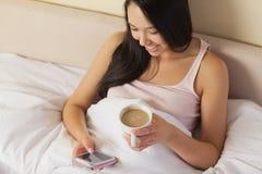 Jeune femme asiatique gaie s'asseyant dans le service de mini-messages de lit sur son smartph photos libres de droits