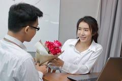 Jeune femme asiatique heureuse acceptant un bouquet des roses rouges de l'ami dans le bureau le jour du ` s de valentine Histoire Photo stock
