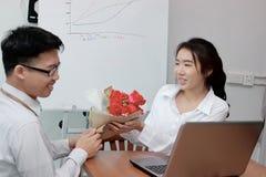 Jeune femme asiatique heureuse acceptant un bouquet des roses rouges de l'ami dans le bureau le jour du ` s de valentine Histoire Photographie stock
