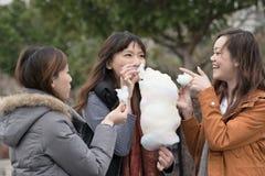 Jeune femme asiatique heureuse mangeant la sucrerie de coton avec ses amis Photo stock