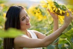 Jeune femme asiatique heureuse souriant et regardant le tournesol dans photos stock