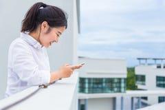 Jeune femme asiatique heureuse vérifiant son media social sur elle téléphone o Photo libre de droits