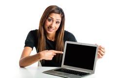 Jeune femme asiatique indiquant l'ordinateur portatif. Image libre de droits
