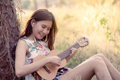 Jeune femme asiatique jouant le guitalele acoustique photos stock
