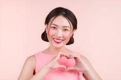 Jeune femme asiatique mignonne avec la main de geste de maquillage de mode faisant h Photos stock