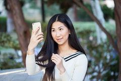 Jeune femme asiatique mignonne en beau parc utilisant son téléphone Photo stock