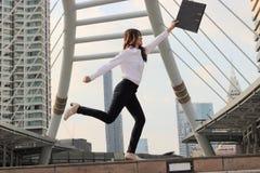 Jeune femme asiatique réussie d'affaires soulevant ses bras avec le fichier document au fond de paysage urbain image libre de droits