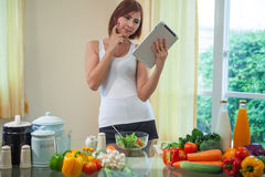 Jeune femme asiatique recherchant une recette Image stock