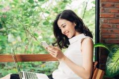 Jeune femme asiatique sûre dans la tenue de détente futée utilisant le smartphon Photos stock