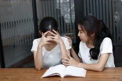 Jeune femme asiatique soulageant son ami déprimé dans le salon Images stock