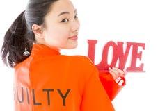 Jeune femme asiatique stockant un texte rouge d'AMOUR dans les prisonniers uniforme Image libre de droits