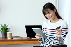 Jeune femme asiatique tenant la carte de crédit et à l'aide du comprimé pour le shopp Photo libre de droits