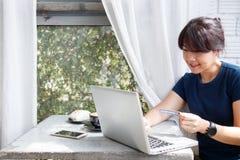Jeune femme asiatique tenant la carte de crédit et à l'aide de l'ordinateur portable tout en se reposant en café Concept en ligne photos libres de droits