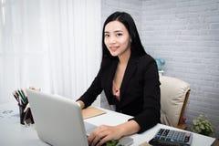 Jeune femme asiatique travaillant à un bureau Images stock