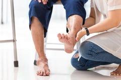 Jeune femme asiatique vérifiant le genou de la femme agée à la maison, femme supérieure recevant le massage par le thérapeute fém image stock