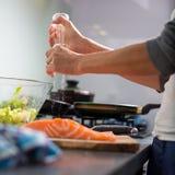 Jeune femme assaisonnant un filet de salomn dans sa cuisine moderne Images stock