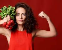 Jeune femme assez gaie de sport posant avec le vert frais de radis photographie stock libre de droits