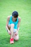 Jeune femme attachant des dentelles des chaussures de course photos stock
