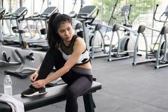Jeune femme attachant la dentelle au centre de fitness athlète féminin pré photos libres de droits