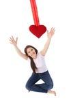 Jeune femme atteignant à l'extérieur pour le sourire rouge de coeur Photos stock