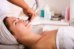 Jeune femme atteignant le nettoyage de peau le salon de beauté Photographie stock