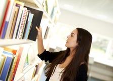 Jeune femme atteignant pour le livre Photographie stock