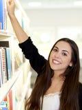 Jeune femme atteignant pour le livre Images stock