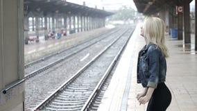 Jeune femme attendant son arrivée d'ami dans la station ferroviaire de plate-forme de train banque de vidéos