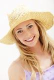 Jeune femme attirant dans le chapeau de paille Images stock