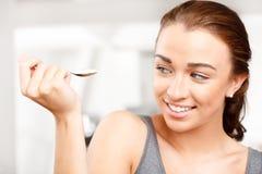 Jeune femme attirant mangeant du yaourt photographie stock libre de droits