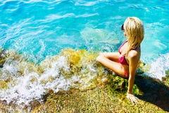 Jeune femme attirant près de l'eau Image stock
