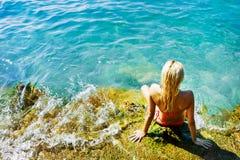 Jeune femme attirant près de l'eau Photo libre de droits