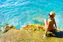 Jeune femme attirant près de l'eau Photos stock