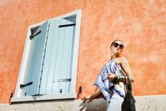Jeune femme attirant près du mur avec l'hublot Image stock