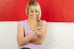 Jeune femme attirant sur le divan avec le téléphone Photo libre de droits