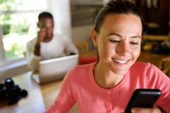 Jeune femme attirante à l'aide du téléphone portable avec l'homme à l'arrière-plan Images stock