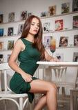 Jeune femme attirante à la mode dans la robe verte se reposant dans le restaurant Belle pose rousse dans le paysage élégant avec  Photo libre de droits