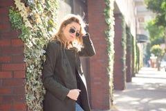 Jeune femme attirante élégante dans des lunettes de soleil se tenant dehors Photo stock