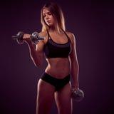 Jeune femme attirante établissant avec des haltères - fitne de bikini Images stock