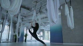 Jeune femme attirante étirant ses jambes utilisant l'hamac de yoga au centre de fitness avec la grande fenêtre du sol au plafond banque de vidéos