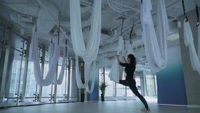 Jeune femme attirante étirant ses jambes utilisant l'hamac de yoga au centre de fitness avec la grande fenêtre du sol au plafond clips vidéos