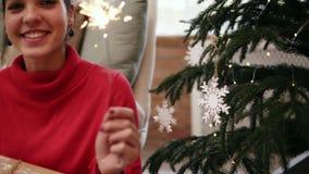 Jeune femme attirante amicale de sourire s'asseyant sur le plancher par l'arbre de Noël célébrant Noël avec des cierges magiques  banque de vidéos