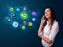 Jeune femme appelant par le téléphone avec de diverses icônes Photographie stock libre de droits