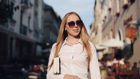 Jeune femme attirante avec des lunettes de soleil tenant le livre et la promenade le long de la vieille ville Étudiant, éducation banque de vidéos