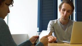 Jeune femme attirante avec l'e-lecteur et l'homme avec l'ordinateur portable parlant en café banque de vidéos
