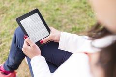 Jeune femme attirante avec l'eBook/comprimé en parc Photographie stock libre de droits