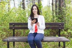 Jeune femme attirante avec l'eBook/comprimé en parc Images libres de droits