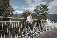 Jeune femme attirante avec la bicyclette sur un pont photo libre de droits